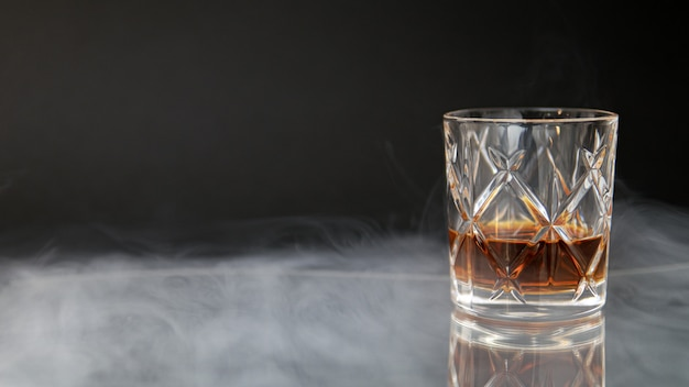 Glass of whiskey on a table surrounded by smoke against a black background