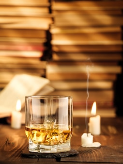 A glass of whiskey on the table with books and burning candles and rays of light. copy space, vertical photo.