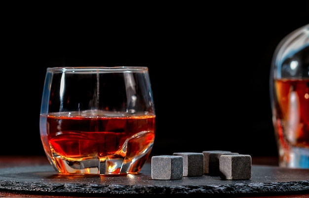 Glass of whiskey with black chilling cubes or reusable ice blocks viewed low angle on a bar counter with copy space on a dark background