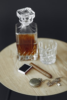 Glass of whiskey with cigar on table. close up photo of alcohol and cigar.