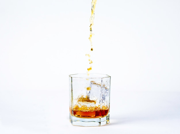 The glass of whiskey with cool ice on the white background