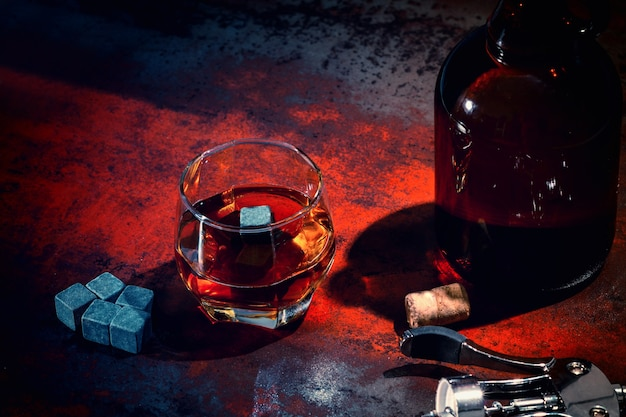 Glass of whiskey with decanter and chilling cubes viewed high angle in red light on an old counter in a pub