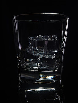 Glass of whiskey with ice on a black background with reflection
