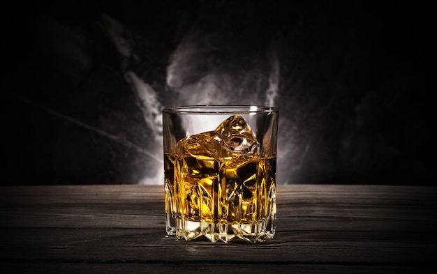 Glass of whiskey with ice on black background