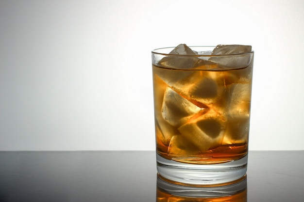 Glass of whiskey with ice copy space