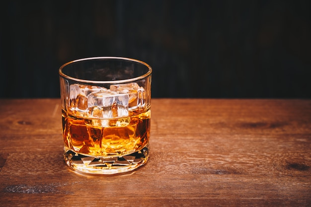 Glass of whiskey with ice cube on wooden table over black background