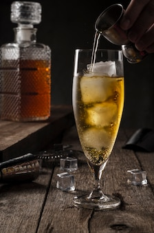 Glass of whiskey with ice cubes being served, some ice cubes loose on the table with bar accessories, bottom with a blurry whiskey bottle.