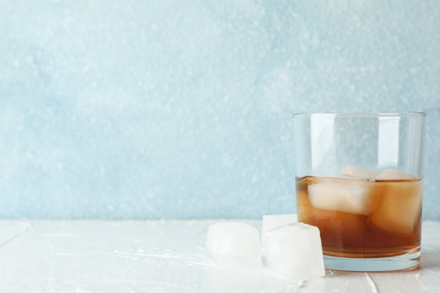 Glass of whiskey with ice cubes on white background, space for text
