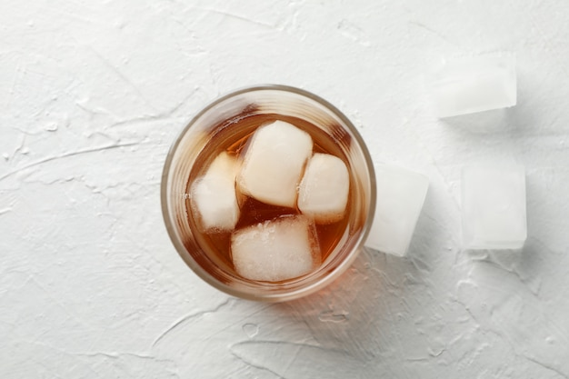 Glass of whiskey with ice cubes on white background, top view