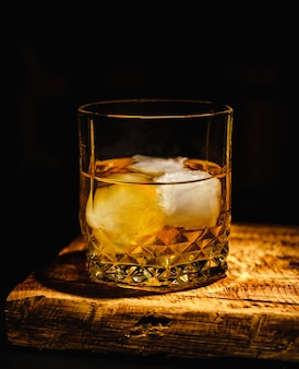 Glass of whiskey with ice cubes on the wooden table