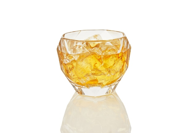 Glass of whiskey with ice isolated on white background with reflection
