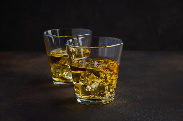 Glass of whiskey with ice on the old rusty background.