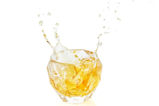 Glass of whiskey with ice and splashes on white background with reflection.