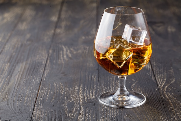 Glass of whiskey with ice on a wooden surface