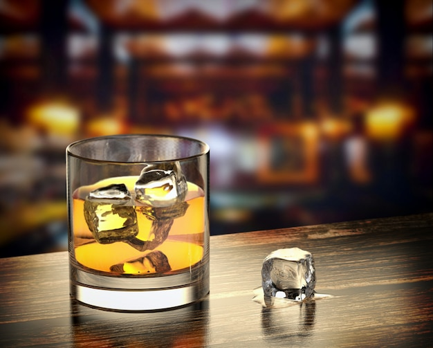 Glass of whiskey with ice on the wooden table with a blurred bar background.