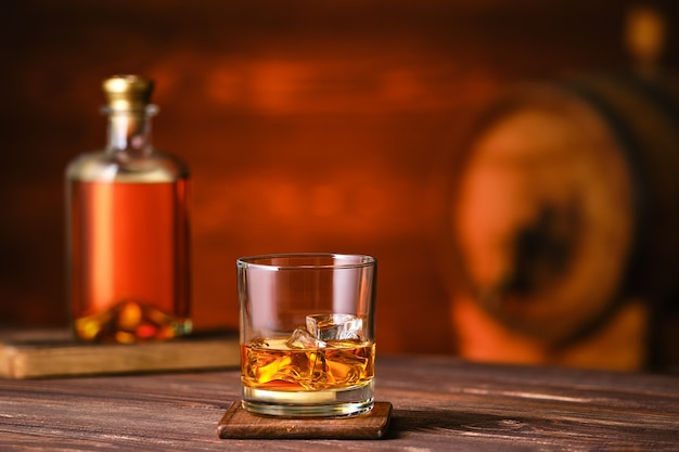 Glass of whiskey with ice on wooden table with bottle and barrel on background