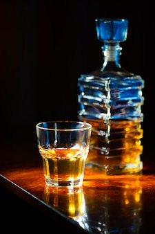 Glass of whiskey with old square carafe on a varnished wooden table