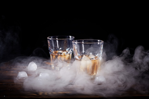 Glass of whiskey with smoke and ice on a wooden table