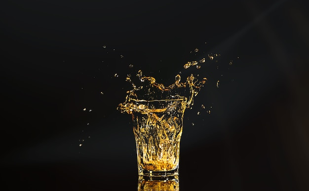 A glass of whiskey with splashes from the ice cube over black space. alcohol splashes. whisky or cognac or another type of alcohol with splashes.