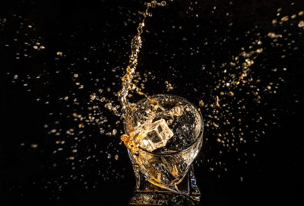 Glass of whiskey with splashes from the ice cubes