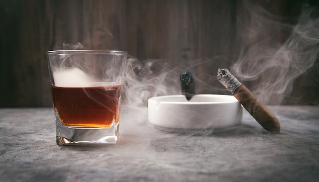 Glass of whisky, ashtray and cigars on the table