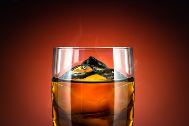 Glass of whisky and ice on red background. close up of alcohol glass with cool drink.