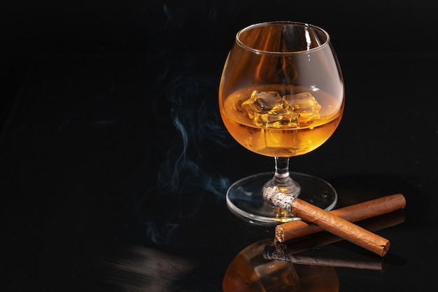 Glass of whisky and lighted cigar on black background close up