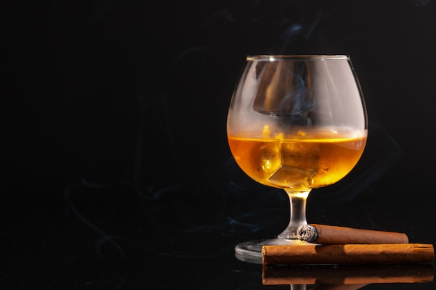 Glass of whisky and lighted cigar on black background