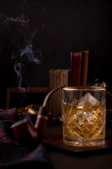A glass of whisky and smoking pipe