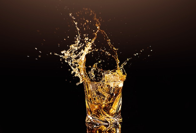 A glass of whisky with splashes from the ice cube