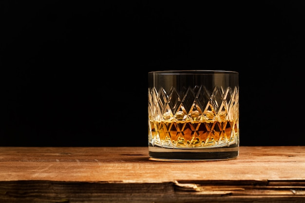 A glass of whisky on a wooden table on a dark