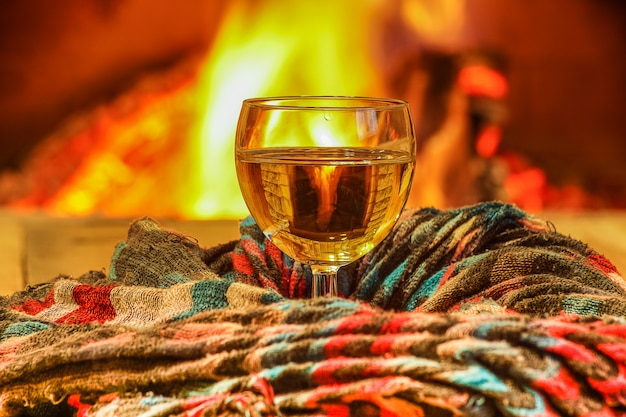 Glass of white wine against cozy fireplace background