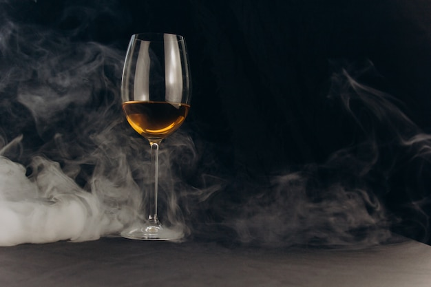 A glass of white wine on a black background. the smoke from the hookah envelops the glass.