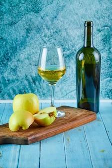 Un bicchiere di vino bianco e una bottiglia con fette di mela sulla parete blu.