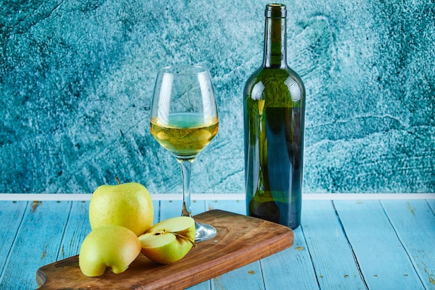 A glass of white wine and bottle with apple slices on blue wall.