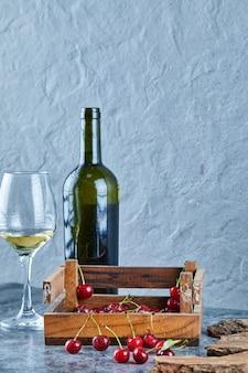 Un bicchiere di vino bianco, bottiglia e scatola di legno di ciliegie sulla superficie blu