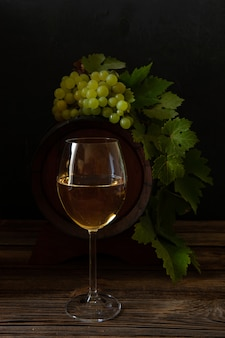 A glass of white wine, a bunch of grapes with leaves and a wine barrel