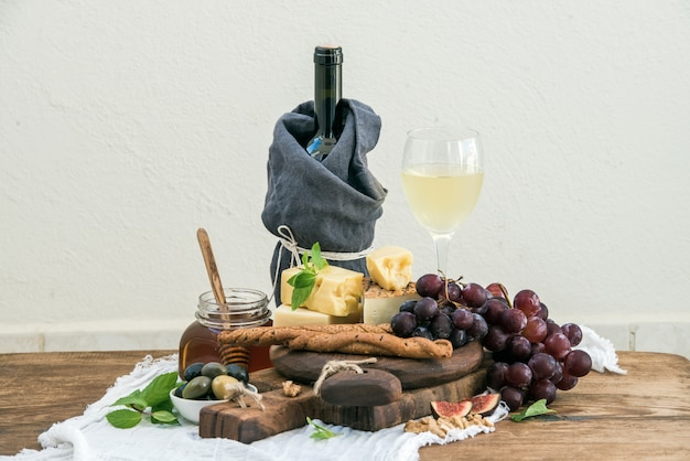 Glass of white wine, cheese board, grapes, fig, strawberries, honey and bread sticks  on rustic wooden table, light wall