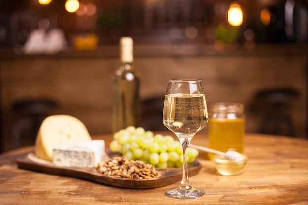 Bicchiere di vino bianco, formaggio e uva sul vecchio tavolo di legno. uva deliziosa. bevanda raffinata. vasetto di miele.