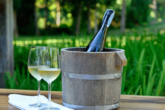 A glass of white wine and wine bottle in ice bucket on wood table