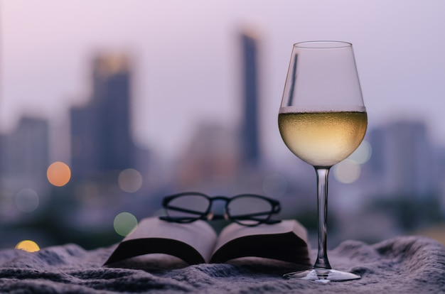 A glass of white wine with book and glasses over a bed with city background.
