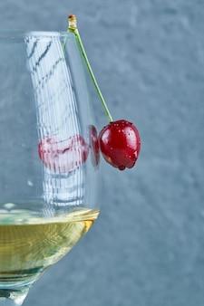 Un bicchiere di vino bianco con bacche di ciliegia sulla superficie blu