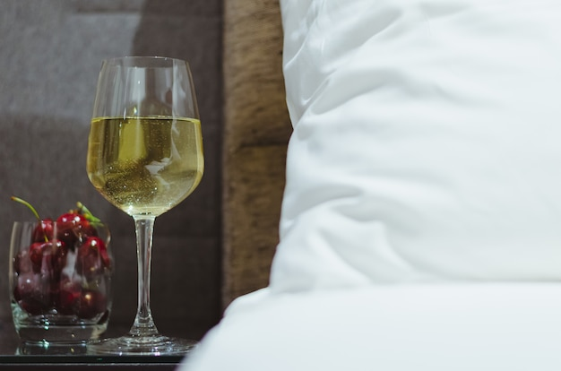 A glass of white wine with cherry fruits on table besides bed with white bedsheet