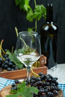 Un bicchiere di vino bianco con frutta da parte.