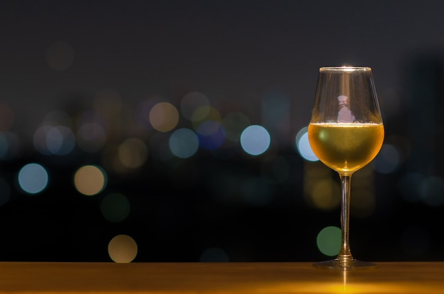 A glass of white wine on wooden table of rooftop bar with colorful bokeh of city light and copyspace