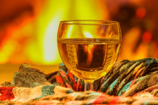 Glass of white wine and wool things near cozy fireplace.