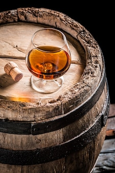 A glass of wine and barrel on wooden table