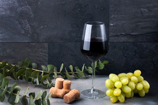 A glass of wine on a black background. grapes pink and green