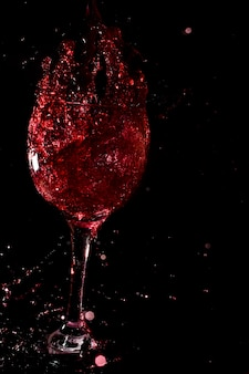 Glass of wine on a black background.