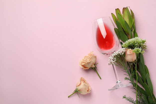 Glass of wine and flowers on pink background